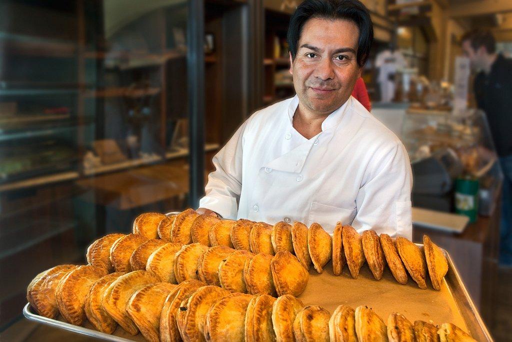 Baker displays tray of empanadas in San Francisco, California