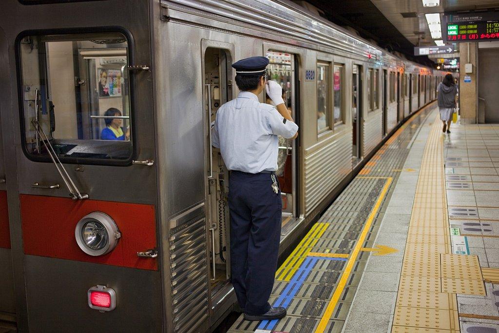 Subway line conductor signals at station in Tokyo, Japan