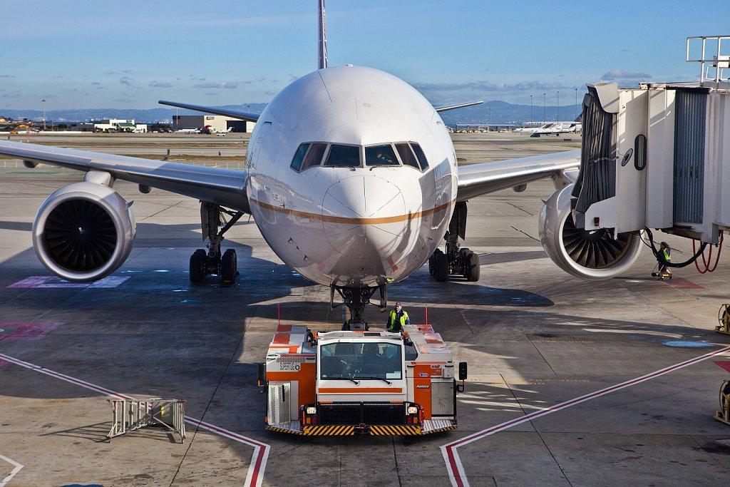 Tug pushing departing airliner at Hong Kong International Airport, Hong Kong, China