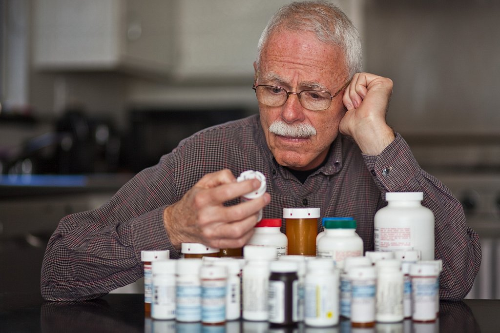 Mature man ponders over too many medications, Los Angeles, California