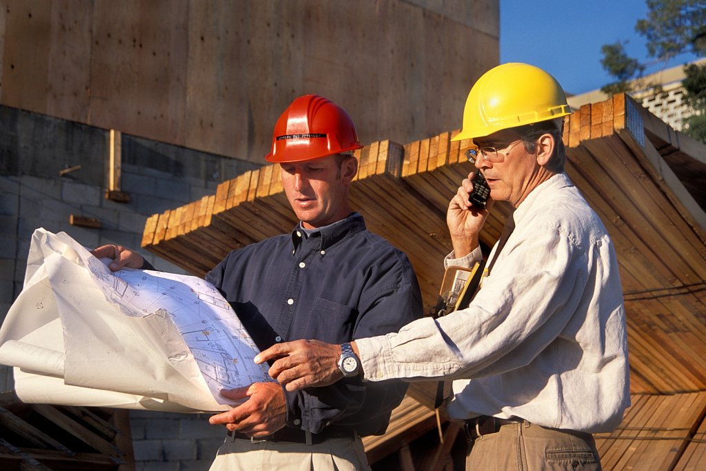 Architect and contractor discuss plan at construction site, Los Angeles