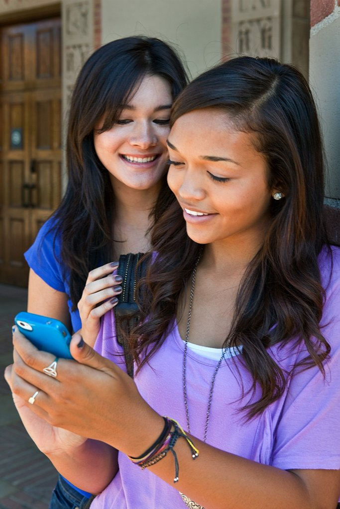 Students check text messages on cell phone