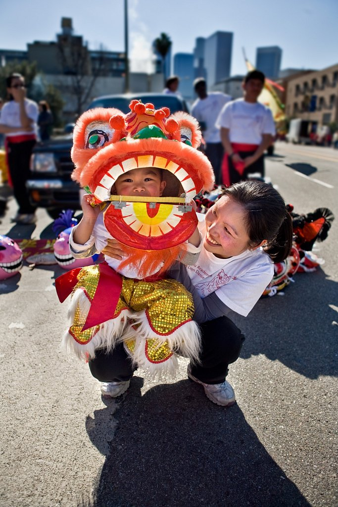 Young boy in lion costume with mother at Chinese New Year parade, Los Angeles, California