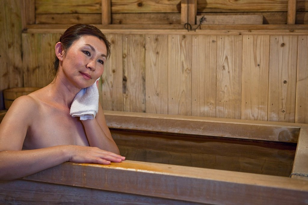 Woman enjoys soaking in hot bath at a onsen in Yufuin, Oita, Japan
