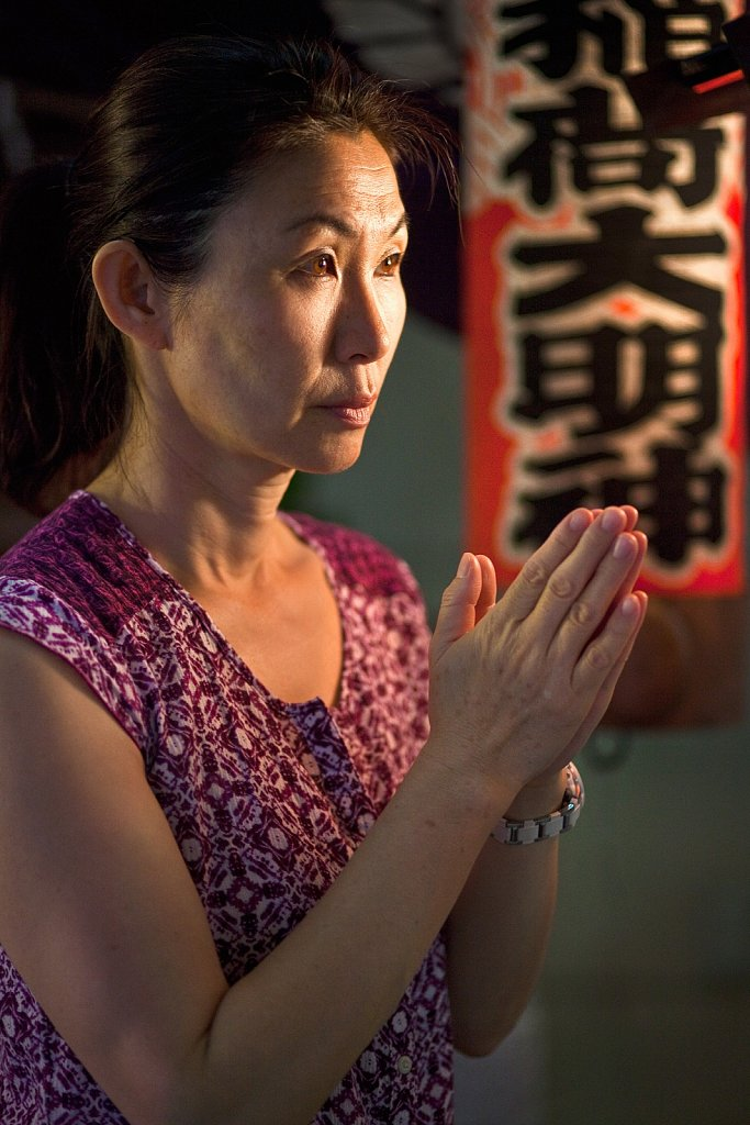 Woman prays at small shrine in Ginza, Tokyo, Japan