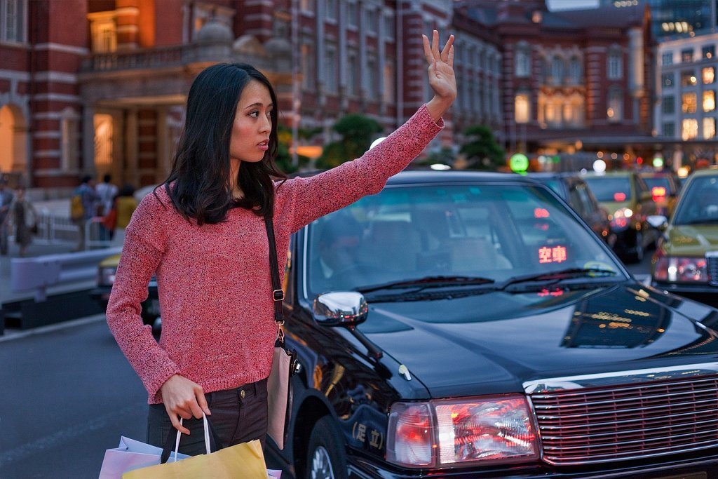 Young Asian woman signals for Taxi in Tokyo, Japan