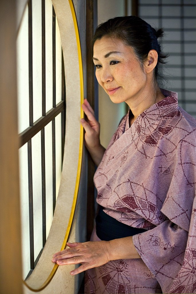 Asian mature woman standing by window in traditional Japanese room, Fukuoka, Japan