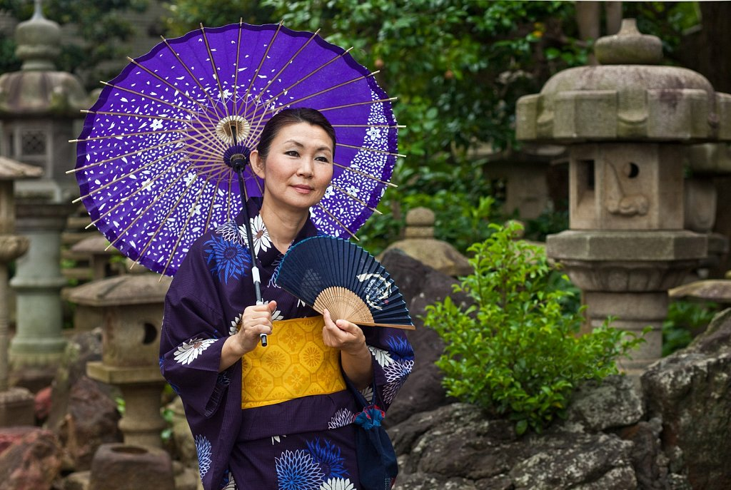 Mature woman in yukata with fan and umbrella at a Temple in Nakaikegami, Tokyo, Japan
