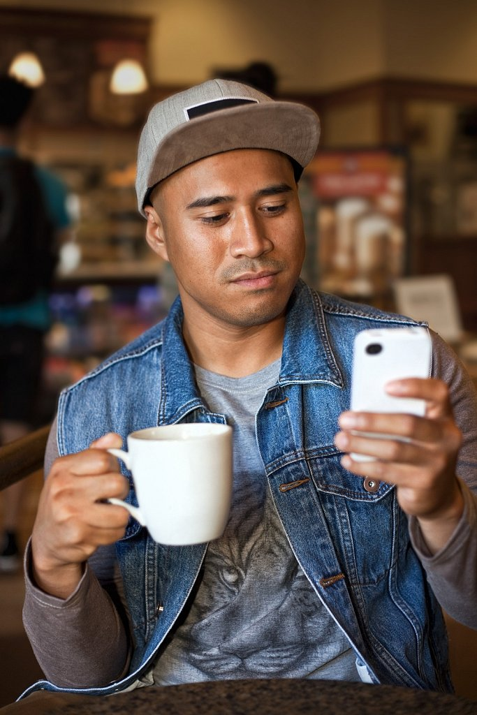 Young Filipino man with cell phone at a coffeeshop in Los Angeles, California