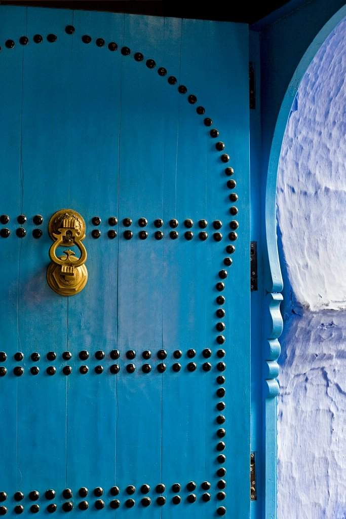 Blue doorway with brass knocker in Chefchaouen, Morocco