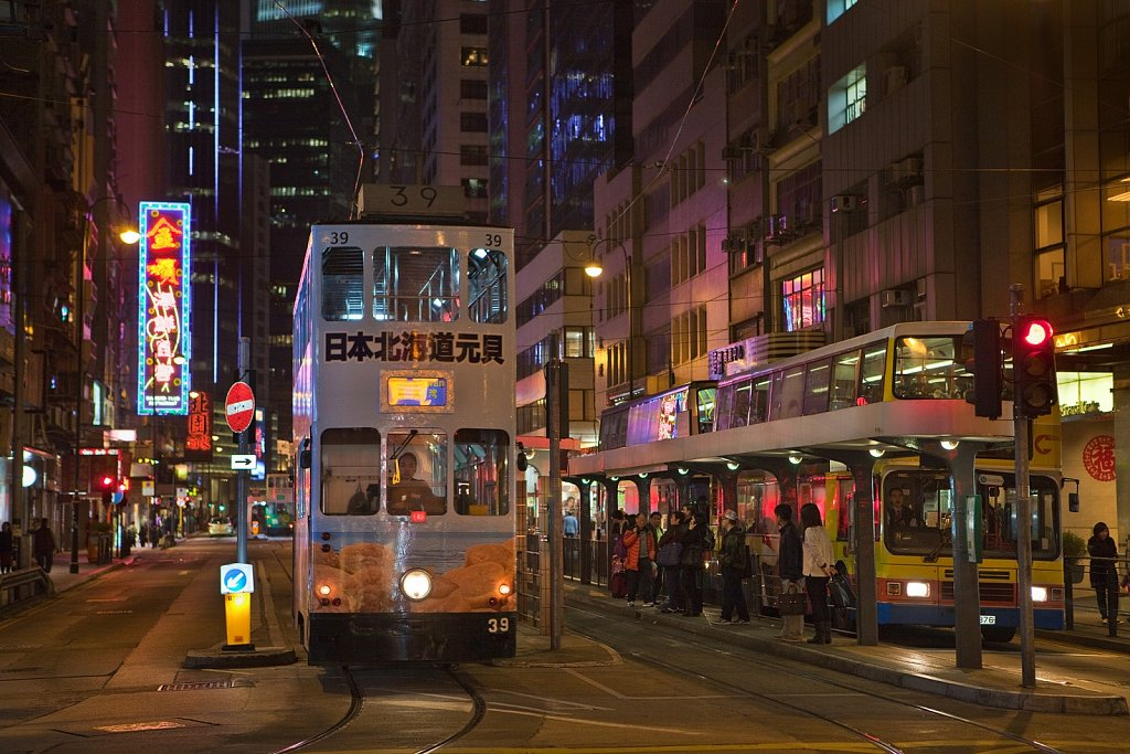 Double-decker tram and buses in the evening on Hong Kong Island, China