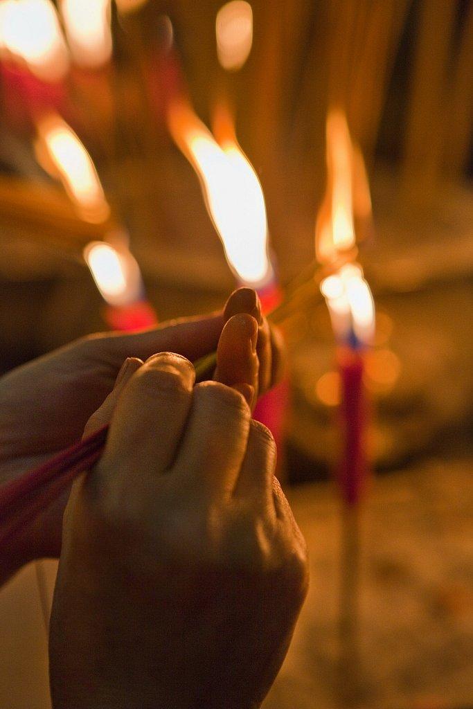 Worshiper lights incense at Man Mo Temple in Hong Kong, China