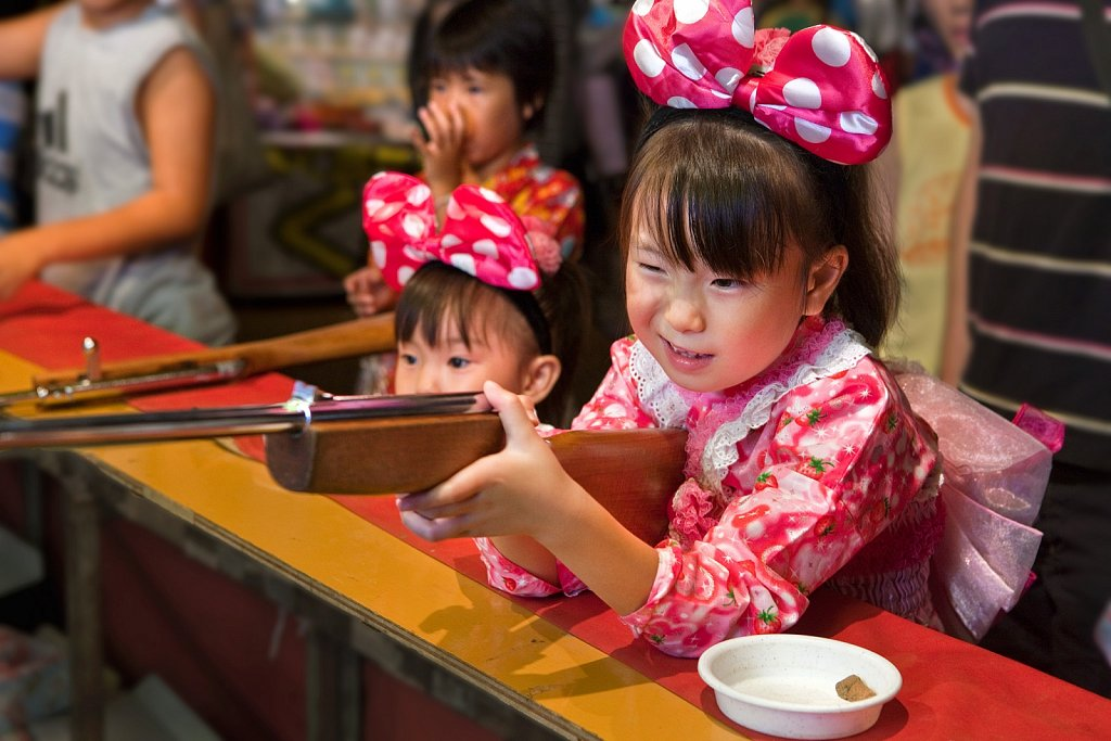 Children shoot corks from toy rifles at Takadanobaba obon festival in Tokyo, Japan