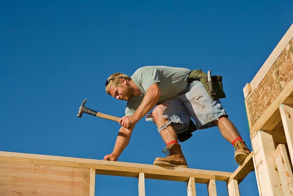 Carpenter works on framing new house